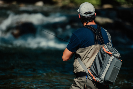Trout-fishing in mountain river in summer time