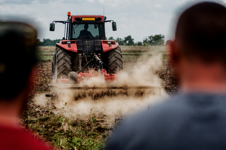 Tractor preparing land for sowing out in field