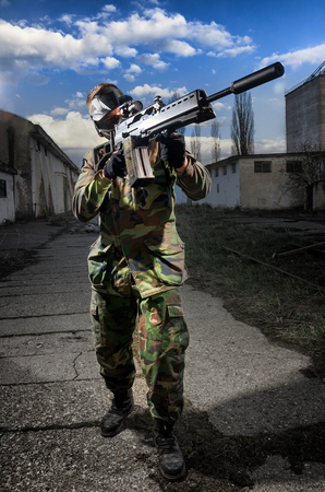 Soldier (airsoft) holding a weapon aiming through the scope lit 新聞圖片