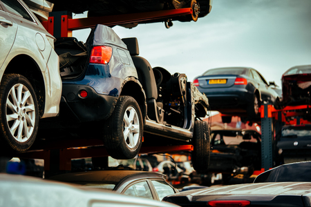 Damaged cars waiting in a scrapyard to be recycled or used for spare part Stock Photo