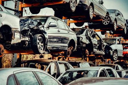 Automóviles dañados esperando en un depósito de chatarra para ser reciclados o usados como repuestos Foto de archivo