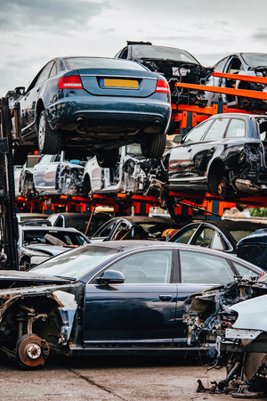 Damaged cars waiting in a scrapyard to be recycled or used for spare part Stock fotó
