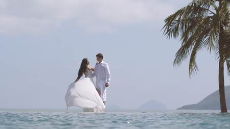 Bride is playing with her long white wedding dress. Young beautiful man and woman hug each other at the beach. Happy loving couple at the honeymoon. Valentines day concept.