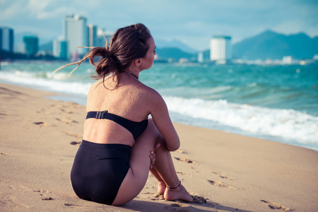 resort life: Woman sitting on the beach in black swimsuit enjoying summer holidays looking at the ocean