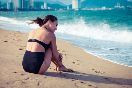 Beautiful woman sitting on the beach in black swimsuit enjoying summer holidays looking at the sea. Stock Photo
