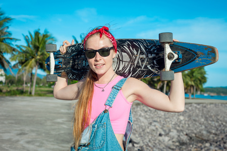 Pretty sexy young woman stand with longboard in front of sea and palms in sunny weather. Stock Photo