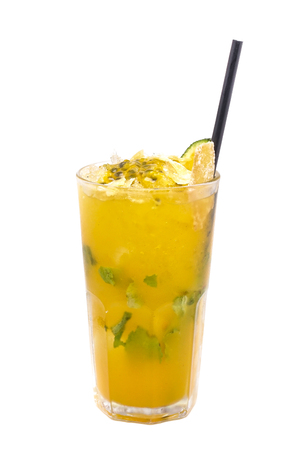 Close up of glass with iced refreshing cocktail with lime, passion fruit and mint.