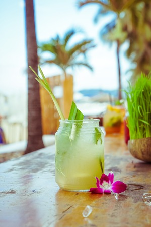 Close up of glass with tropical refreshing lemongrass coctail with mint, lime and flower decoration on palm beach background Stock Photo
