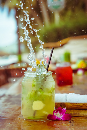 non alcoholic: Close up of glass with tropical refreshing lemongrass coctail with mint, ginger and flower decoration with splashes on palm beach bar background