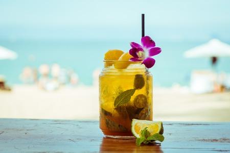 Cierre de vidrio con refrescante cóctel de naranja con decoración de Lima, melocotón y flor en el fondo de la playa del mar