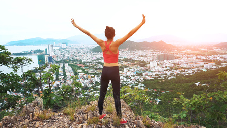 Woman runner raise hands up in the air. Female run on top of the mountain