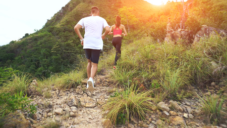 Young couple running on mountain trail. Stock Photo