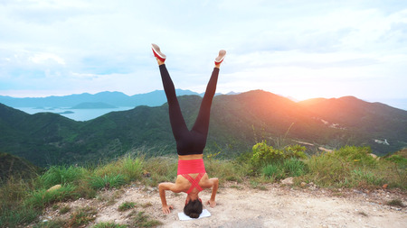 winning location: Young woman practicing yoga headstand on top of rock. Landscape mountain view.