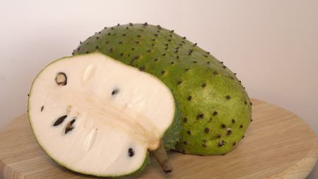 Soursop, Annona muricata L with slice on wooden cutting board Stock Photo