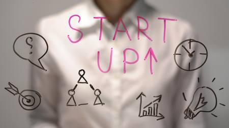 illustrates: Woman wrote Start Up and red arrow up on transparent screen. Businesswoman write on board. Stock Photo