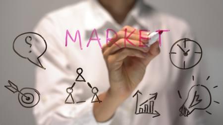Woman writing Market on transparent screen. Businesswoman write on board. Stock Photo