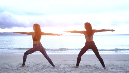 Young women doing yoga on a beach wearing a sports wear.