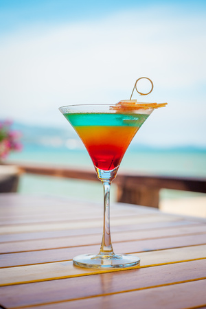 Close up of glass with refreshing layered cocktail with orange and cherry.