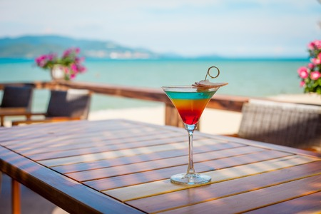 Close up of glass with refreshing layered cocktail with orange and cherry. Imagens