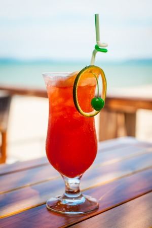 Close up of glass with refreshing orange cocktail with cherry on table on beach.