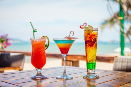 non alcoholic: Set of iced cocktails: layered with lime, orange, blue and red cocktail on beach