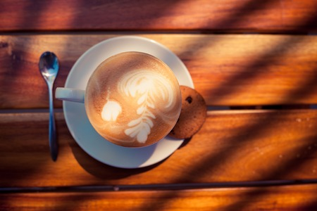 A cup of coffee with pattern in a white cup with cookie on wooden background