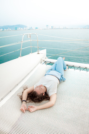 Young woman lay on cruise ship deck while travelling in the sea