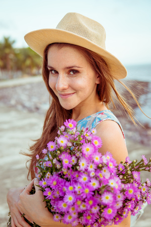Beautiful enigmatic woman holding flowers Stock Photo
