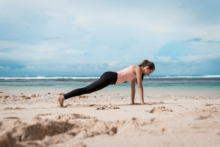 Fitness woman doing yoga exercises. Girl training her abs exercising core muscles with the plank pose.