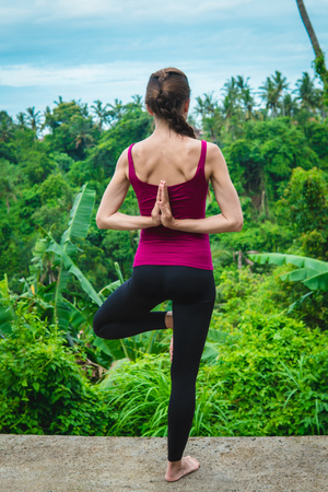 Yoga concept. Tree pose with namaste behind the back