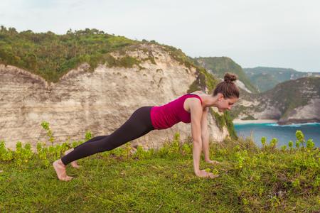 Fitness woman doing yoga exercises. Girl training plank pose.