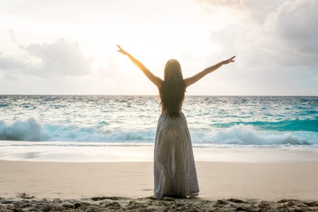 Woman in long dress with raised arms standing on beach and looking to ocean Stockfoto