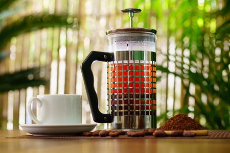 French press brewed cacao nibs and white cup of cocoa on wooden table