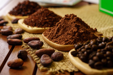 Cacao powder, cocoa nibs, and coffee beans on wooden plates on burlap Stock Photo