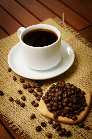 Cup of black coffee and coffee beans on burlap