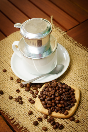 Cup of vietnamese coffee with phin and coffee beans on burlap Stock Photo