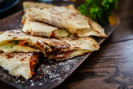 Mexican cuisine. Grilled quesadillas, tortillas with cheese, on wooden board. Stock Photo