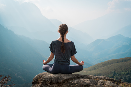 Woman meditates in yoga in front of moutains