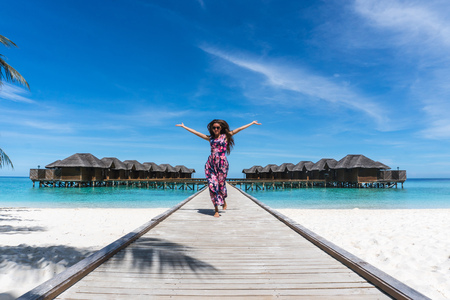 Happy woman with raised hands on bridge on beach in Maldives