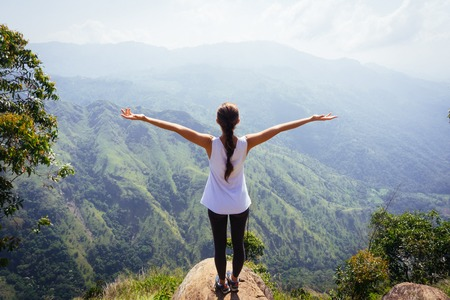 Sporty woman standing with raised arms on the top oh hill Stock Photo