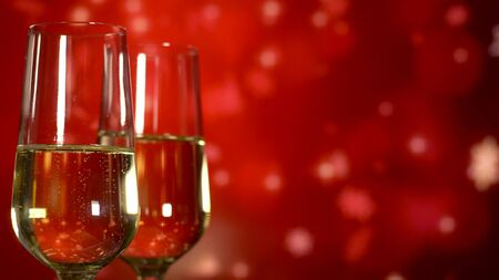 Two glasses with sparkling champagne over red holiday background. Close up
