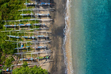 Aerial shot of tropical bay with sandy beach, boats. Village of Amed, Bali.