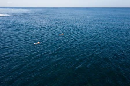 Aerial view of surfers in tropical ocean. Bali, Indonesia