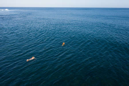 Aerial view of surfers in tropical ocean waiting for waves. Bali, Indonesia