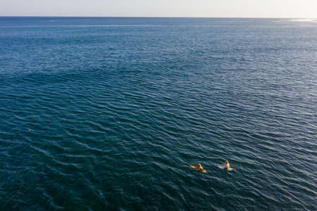 Two surfers in tropical ocean waiting for waves. Bali, Indonesia. Aerial view