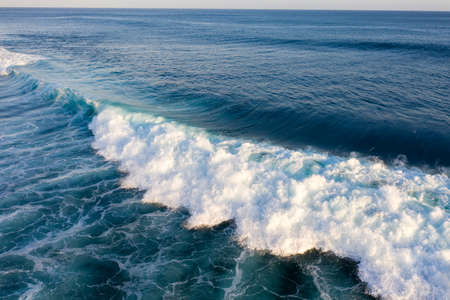 Aerial view of giant ocean waves crashing and foaming