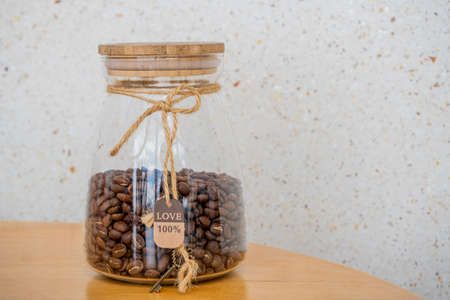 Coffee beans in glass jar on a wooden table. 100 percent Love sign and key
