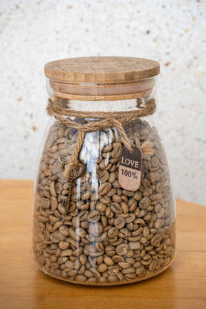 Green coffee beans in glass jar on a wooden table. Love sign on the rope