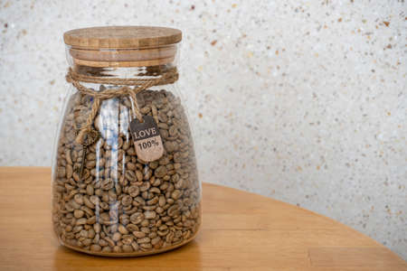 Coffee beans in glass jar on a wooden table. 100 percent Love sign on the rope
