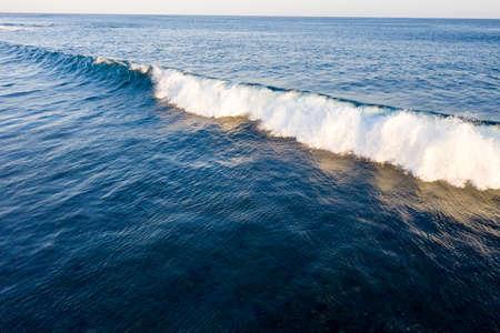 Aerial view of giant ocean wave foaming
